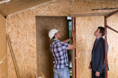 Architect and Worker Checking Levels on Door Frame Stock Image