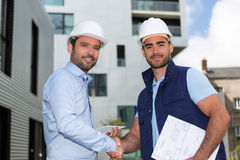 Architect and worker handshaking on construction site Royalty Free Stock Image