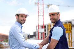Architect and worker handshaking on construction site Royalty Free Stock Photos