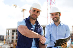 Architect and worker handshaking on construction site Royalty Free Stock Photo