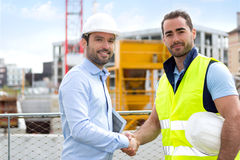 Architect and worker handshaking on construction site Stock Images