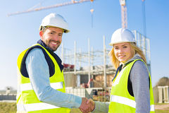 Architect and worker handshaking on construction site Stock Image