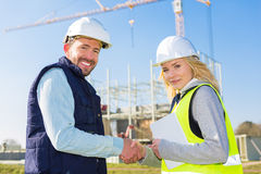 Architect and worker handshaking on construction site Stock Photos