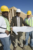 Architect And Workers With Blueprint At Site Stock Photo