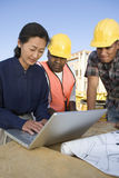 Architect With Workers Using Laptop At Site Stock Photos
