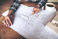 Architect working on an architecture model with shop drawing paper and coffee cup on table. An architect working on an architecture model with shop drawing paper royalty free stock image
