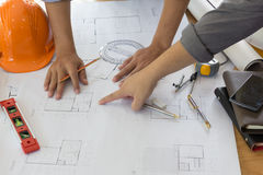 Architect working on blueprint. Architects workplace - architectural project, blueprints, ruler, calculator, laptop and divider co. Mpass. Construction concept Royalty Free Stock Photography