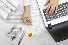 Architect working on blueprint. Architects workplace - architectural project, blueprints, ruler, calculator, laptop and Stock Photos