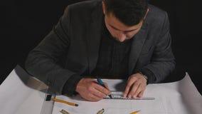 Architect working on blueprint on black background.  stock video