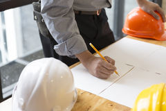 Architect working on blueprint of construction project in workpl Royalty Free Stock Photo
