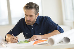Architect Working On Blueprint At Desk Royalty Free Stock Photo