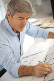 Architect working with blueprint. Architect working on blueprint in office Stock Photography