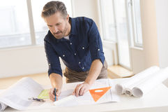 Architect Working On Blueprint At Office Desk Stock Photos