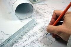 Architect Working With Blueprints 2. Architect working with blueprints.  Closeup with intentional focus on pencil and architect ruler Stock Photo