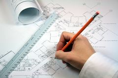 Architect Working With Blueprints. Workspace includes rolled blueprints and architect ruler Stock Photo