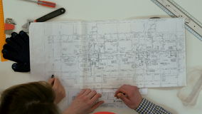 Architect working on blueprints when female colleague bringing more drawings stock video footage