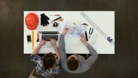 Architect working on blueprints while female colleague typing on laptop stock footage