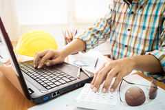 Architect working on calculator and laptop with construction plan. In office. Construction concept royalty free stock images