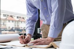 Architect working on construction plan at office. engineer inspe. Ct blueprint at workplace. young man sketching real estate project. drawing compass, vernier Royalty Free Stock Photo