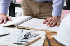 Architect working on construction plan at office. engineer inspe. Ct blueprint at workplace. young man sketching real estate project. drawing compass, vernier Stock Photos