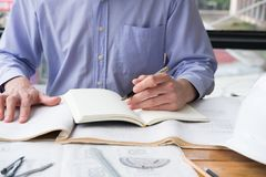 Architect working on construction plan at office. engineer inspe. Ct blueprint at workplace. young man sketching real estate project. drawing compass, vernier Stock Images
