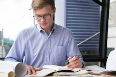 Architect working on construction plan at office. engineer inspe. Ct blueprint at workplace. young man sketching real estate project. drawing compass, vernier Stock Photography