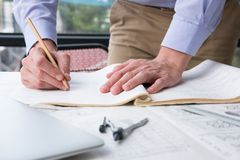 Architect working on construction plan at office. engineer inspe. Ct blueprint at workplace. young man sketching real estate project. drawing compass, vernier Royalty Free Stock Photos