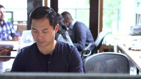 Architect Working At Desk With Meeting In Background stock footage