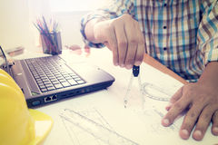 Architect working with dividers on construction plan. In office Stock Photos