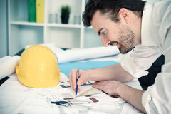 Architect working on his projects papers with compass. Architect working on his projects papers Royalty Free Stock Photo