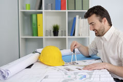 Architect working on his projects. Papers with compass Royalty Free Stock Photos