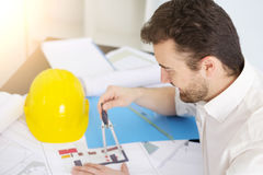 Architect working on his projects papers. With compass Royalty Free Stock Image