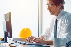 Architect and construction engineer working in office. Architect working in office, construction engineer working with desktop pc computer making a construction Royalty Free Stock Photos