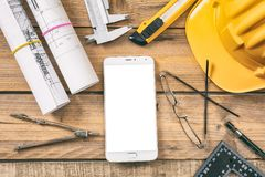 Architect workplace. Smartphone with white, blank screen, project construction blueprints and engineering tools on wooden desk, co royalty free stock images