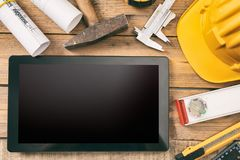 Architect workplace. Tablet with black blank screen, project construction blueprints and engineering tools on wooden desk, copy sp stock photos