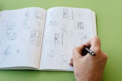 Architect works drawing sketches. On notebook on green  background Royalty Free Stock Photos