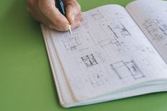 Architect works drawing sketches. On notebook on green  background Royalty Free Stock Photo