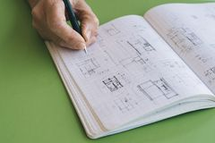 Architect works drawing sketches. On notebook on green  background Stock Photo