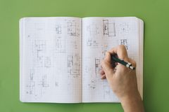 Architect works drawing sketches. On notebook on green  background. Flat lay Stock Photo