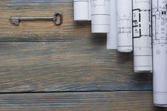 Architect worplace top view. Architectural project, blueprints, blueprint rolls and key on wooden desk table Stock Images