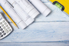 Architect worplace top view. Architectural project, blueprints, blueprint rolls on wooden desk table. Construction. Background. Engineering tools. Copy space Stock Image