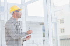 Architect writing on clipboard while looking through office window Stock Photos