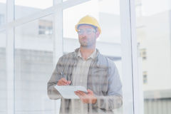 Architect writing on clipboard in office Royalty Free Stock Photos