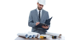 Architect writing report and reading architecture plan of building. Stock Images