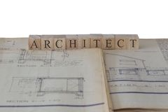 Architect written on wooden blocks on house extension building plans blueprints. With a white background stock images