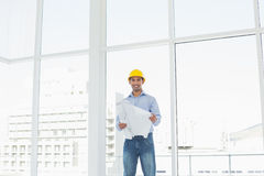 Architect in yellow hard hat with blueprint in office. Portrait of a smiling young architect in yellow hard hat with blueprint in a bright office Stock Image