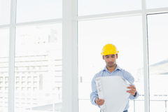 Architect in yellow hard hat looking at blueprint in office Royalty Free Stock Image