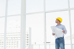 Architect in yellow hard hat with plans looking up at window Royalty Free Stock Photo