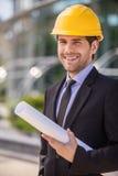 Architect in yellow hardhat holding plan. Royalty Free Stock Photo
