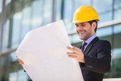Architect in yellow hardhat holding plan. Royalty Free Stock Images